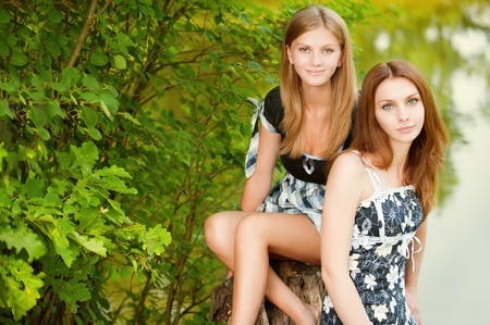 Two beautiful girls sit on stub about pond in summer city park. photo