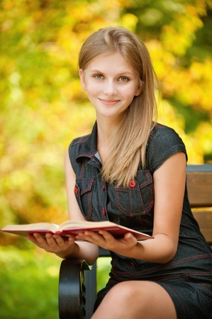 Young beautiful woman reads book in summer city park photo