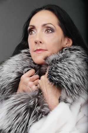 Portrait of beautiful elderly dark-haired woman in clothes with fluffy fur collar. photo