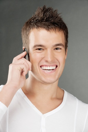 Beautiful young man in white clothes laughs and talks by mobile phone. photo