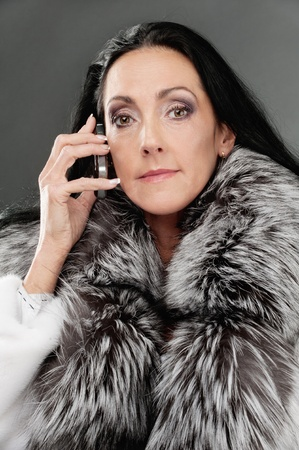 Portrait of beautiful elderly dark-haired woman in clothes with fluffy fur collar speak mobile phone. photo