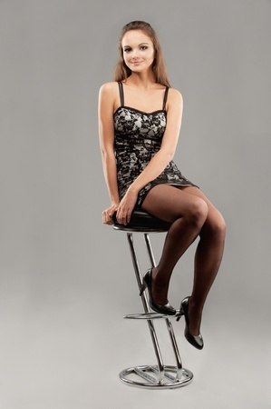 Young beautiful woman sits on bar chair and smiles, on gray background. photo