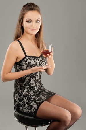 Young beautiful woman drinks wine from wine glass. photo
