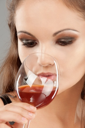 Young beautiful woman drinks wine from wine glass, close up. Stock Photo - 9411850