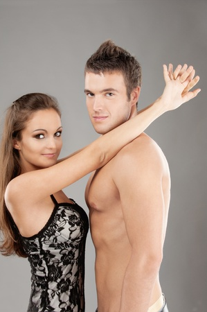 Portrait young beautiful couple on gray background. Stock Photo - 9412414