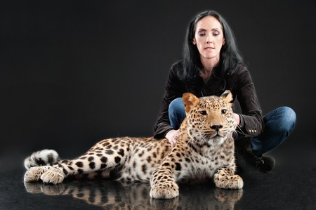 phlegmatic: Mature woman near to spotty leopard, on studio.