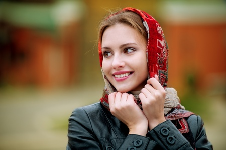 joyfully: The young smiling woman in a red scarf on walk