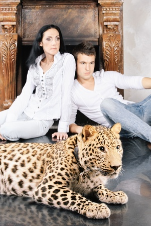phlegmatic: Mature woman and young man near to spotty leopard, on studio.