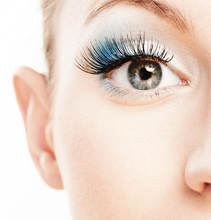 eye lashes: Eye and nose of beautiful young woman close up, soiled by green cosmetics. Stock Photo