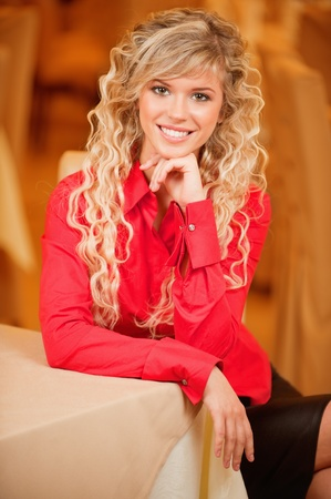Portrait of charming smiling curly-haired young woman with curly hair, sitting at table against beautiful interior. Stock Photo - 9451015