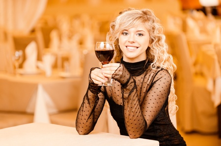 Charming smiling young woman in black clothes with red wine glass sits at magnificent restaurant. photo