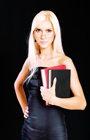 Fine blonde in glasses with book, it is isolated on black background. photo