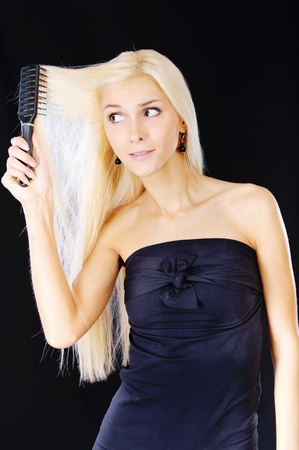 Nice young woman combs hair, it is isolated on black background. photo