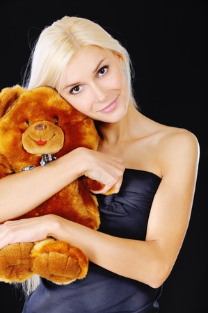 Beautiful blonde holds in hands plush bear, it is isolated on black background. photo