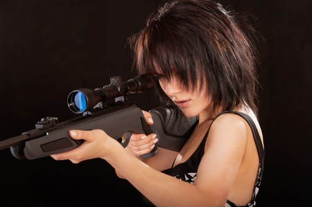 Charming girl presses cock of rifle, is isolated on black background. photo