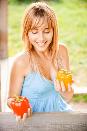 blindly: Young beautiful woman hold two red sweet peppers, on green background.