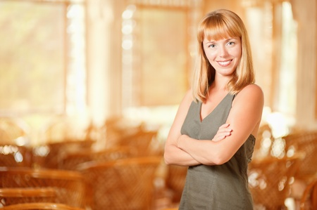 Beautiful young smiling woman has crossed hands on breast, against magnificent interior. photo