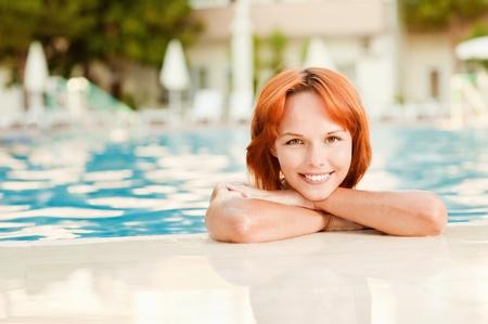 Young beautiful smiling woman in bikini in warm pool on resort. photo