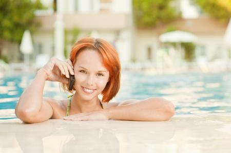 Young beautiful smiling woman in bikini in warm pool on resort and talk in mobile phone. photo