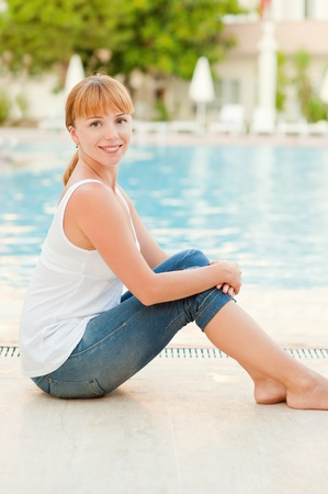 Young beautiful smiling woman in jeans nearby warm pool on resort. photo