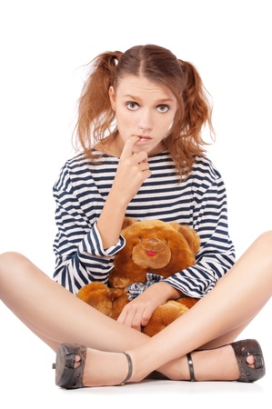 Beautiful girl sits and embraces plush bear, it is isolated on white background. photo