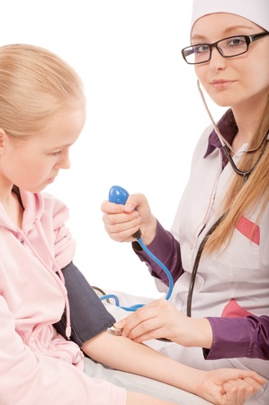 portrait of young female pediatrician checking up blood pressure of child girl patient on white photo