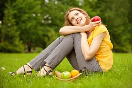 Portrait of girl with basket apples against green grass.