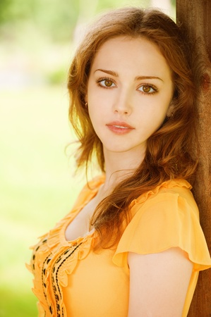 beautiful girl sitting on a park bench leaning on wooden wall