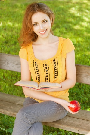 beautiful young girl-student read the book on a park bench with an apple in his hand on the background of green nature photo