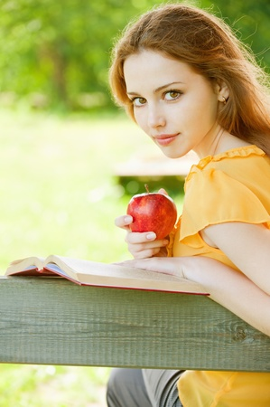 beautiful young girl-student read the book on a park bench with an apple in his hand on the background of green nature