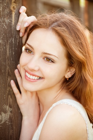 leans: Portrait of smiling young woman, leans about wooden wall Stock Photo