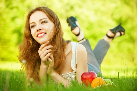 girl lying: A beautiful young girl lying on the grass beside a basket of fruit is, on a background of green nature