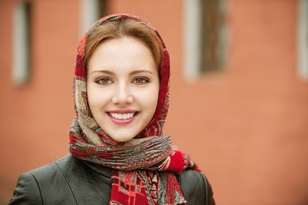 Portrait of smiling charming young woman in headscarf on red background. photo