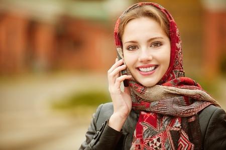 conversa: Joven hermosa mujer sonriente en conversaciones abigarrada pa�uelo rojo en telefon�a celular, contra las estructuras de la ciudad. Foto de archivo