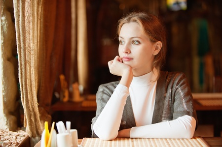Young beautiful woman sits in cozy cafe, looks out of window and drinks hot tea from cup. photo