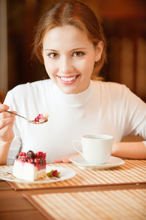 Charming smiling girl sits at table in cafe and beret spoon pie slice. Near to her there is tea cup. photo
