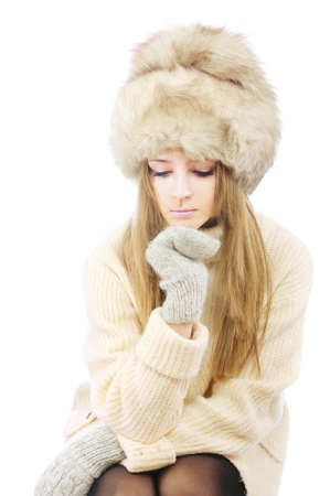 reflects: Beautiful young woman in fur cap and sweater to reflects, isolated on white background.
