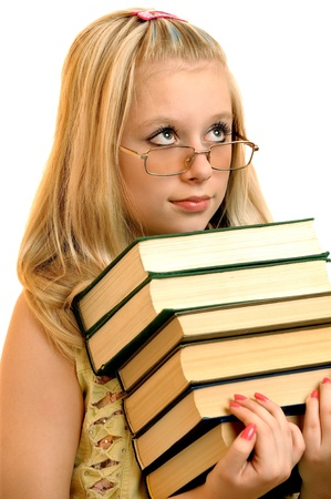 Young schoolgirl in glasses holds some books, it is isolated on white background. photo