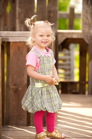 Little girl in wooden children's small town. Stock Photo - 9659593