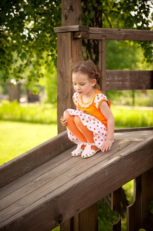 goes: Small girl goes down on wooden childrens hill. Stock Photo