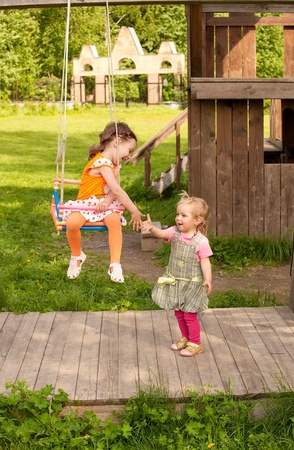 gives: Little girl sits on swing and gives a hand to sister. Stock Photo