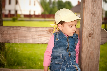 Sad little girl sits on bench in summer garden. photo