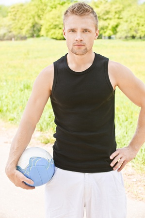 Young beautiful man with volleyball ball, against summer city park. photo