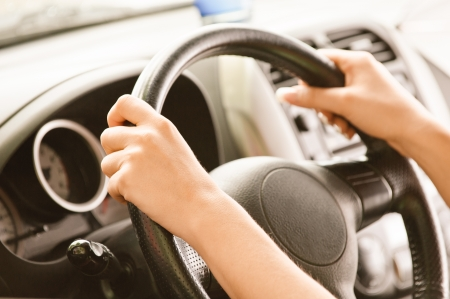 driving school: Wheel of car from hand of driver.