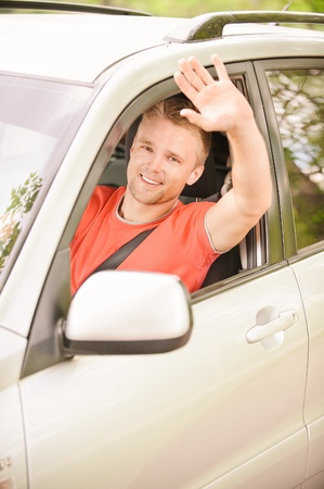 Driver of car waves hand as a sign of greeting. photo