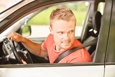 Driver of car looks back and smiles. Stock Photo - 9659591