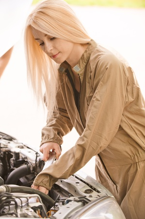 Woman car mechanician repairs engine of car and smiles. photo