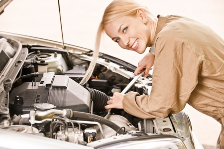 Woman car mechanician repairs engine of car and smiles.