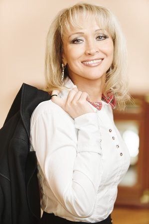 Portrait of beautiful smiling mature business woman in white shirt with jacket , against magnificent interior. Stock Photo - 9659564