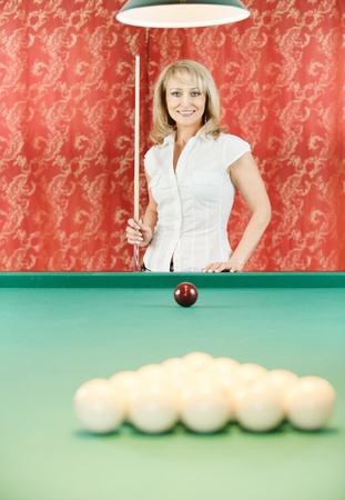 Mature beautiful woman plays billiards in room. photo